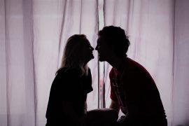 Jeune couple d'amoureux qui s'embrassent dans la pénombre