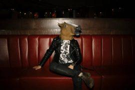Homme assis sur un canapé en cuir rouge, avec un masque de cheval sur la tête