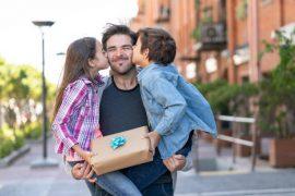Deux enfants qui offrent un cadeau à leur papa pour la fête des pères