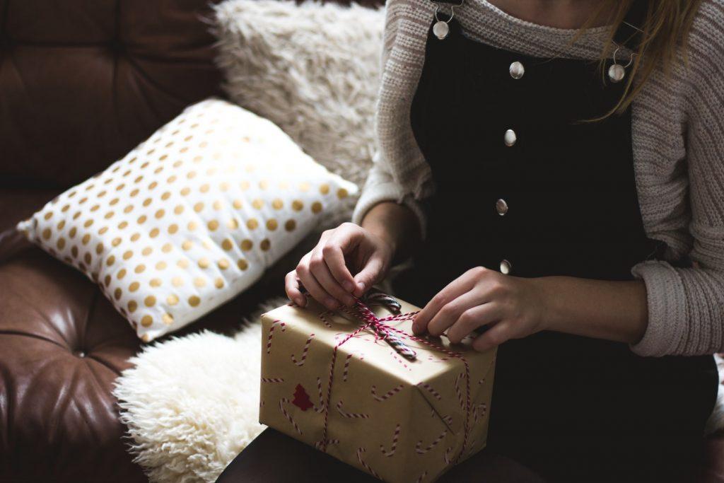 Jeune femme qui ouvre son cadeau de Noël