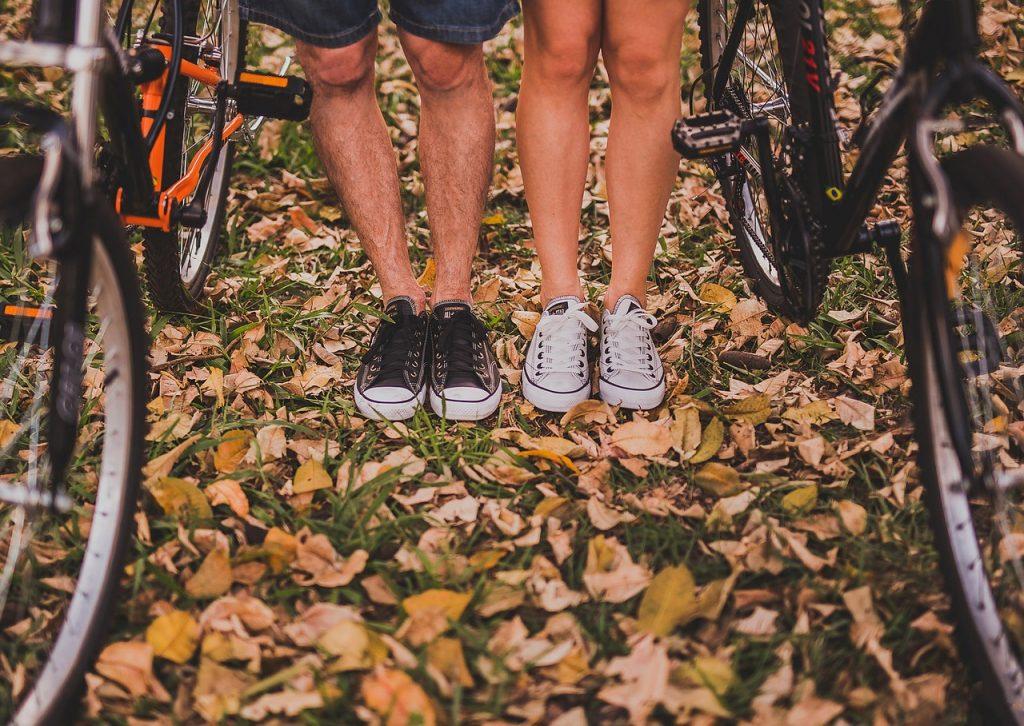 vue sur le bas des jambes d'un homme et d'une femme portant des baskets à côté de vélos
